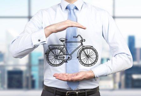 Photo pour Une personne en vêtements formels tient une bicyclette esquissée entre ses mains. Un bureau panoramique moderne est flou sur le fond. Un concept de moyens respectueux de l'environnement de déplacements et les voyages. - image libre de droit