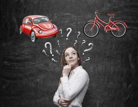 A beautiful woman is trying to chose the most suitable way for travelling or commuting. Two sketches of a car and a bicycle are drawn on the black chalkboard.