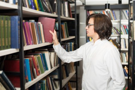 young man with dark hair choosing a book standing between shelve