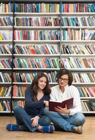 Photo pour Souriante jeune fille et jeune homme assis par terre dans la bibliothèque les jambes croisées en lisant un livre ouvert à la main, elle pointe une ligne, des étagères à l'arrière-plan, un concept de lecture - image libre de droit