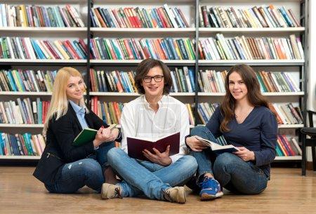 Photo pour Deux jeunes filles souriantes et un jeune homme souriant assis par terre dans la bibliothèque avec les jambes croisées lisant chacune un livre ouvert dans leurs mains, des étagères en arrière-plan, un concept de lecture - image libre de droit