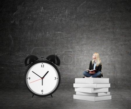 woman sitting on pile of books, big alarm clock  right