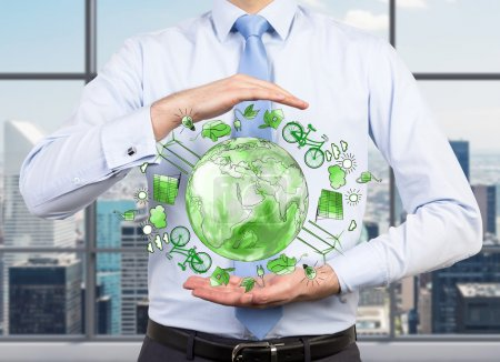 Foto de Hombre como si sostuviera una esfera con una imagen verde de iconos de energía ecológica dispuestos en círculo, tierra en el centro, concepto de ambiente limpio y seguro, vista al pecho - Imagen libre de derechos