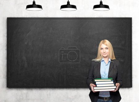 girl with books in front of blackboard