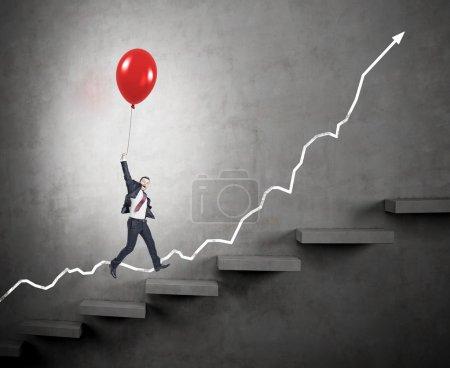 Photo pour Homme d'affaires en costume sous les projecteurs volant heureux tenant un ballon rouge au-dessus de l'échelle carrer, tendance positive à l'arrière, fond sombre, concept de succès et de croissance de carrière - image libre de droit
