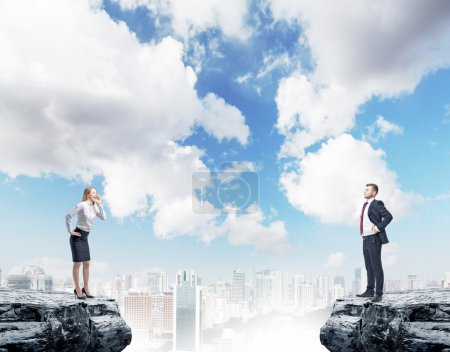two businesspeople standing on rock on city background