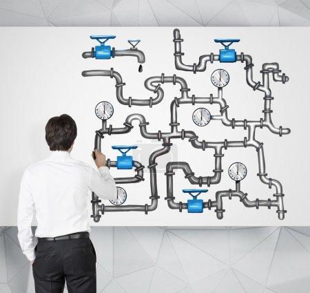 Photo pour Homme debout devant une illustration de pipeline sophistiqué sur le fond blanc, dessin. Vue de derrière. Concept de transport pétrolier - image libre de droit