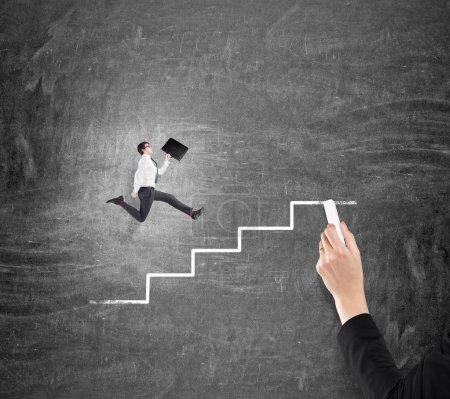 Photo pour Jeune homme d'affaires avec un dossier montant un escalier tracé le long d'un tableau noir, dessinant à la main des marches avec une craie. Concept de croissance de carrière . - image libre de droit