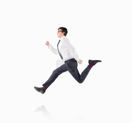 A young handsome businessman wearing a shirt and glasses as if running. Concept of approaching an aim.