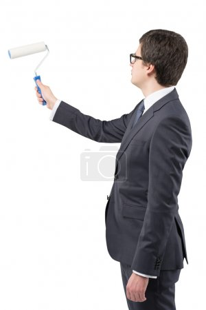 A young businessman starting to draw something on a blank white wall with a roller, Side view. Concept of a new start.
