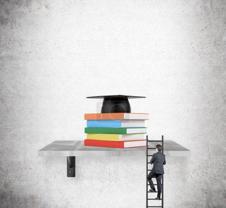 Photo pour Une pile de livres en couvertures colorées sur une étagère, un chapeau académique au-dessus. Un homme monte une échelle pour atteindre l'étagère. Contexte concret. Concept d'éducation . - image libre de droit