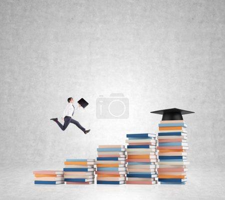 Photo pour Jeune homme avec un dossier à la main monter les escaliers faits de piles de livres de différentes tailles, chapeau de graduation sur le plus haut, fond en béton. Concept d'enseignement supérieur . - image libre de droit