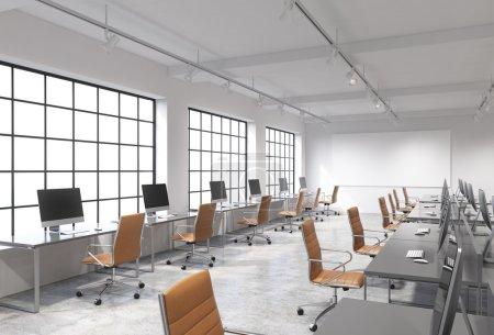 Photo pour Trois rangées de tables d'ordinateur dans un bureau moderne moderne d'espace ouvert de lumière, l'un d'eux le long de la fenêtre. Grand écran blanc sur le mur. Concept de travail. - image libre de droit