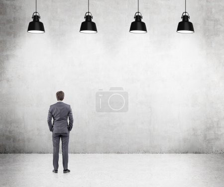 Young businessman standing with his hands in pockets front of a concrete wall, five lamps above.