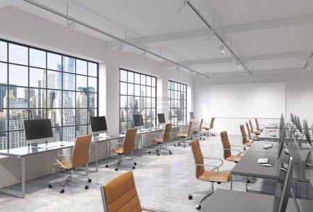 Photo pour Trois rangées de tables d'ordinateur dans un bureau moderne moderne d'espace ouvert de lumière, l'un d'eux le long de la fenêtre. Grand écran blanc sur le mur. Vue de New York. Concept de travail. - image libre de droit
