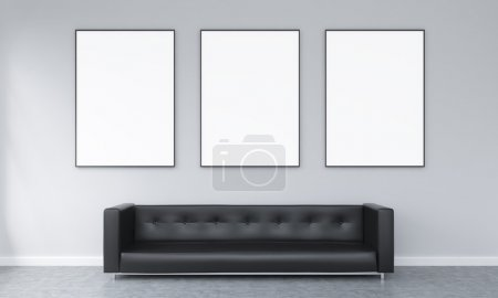 Three blank frames hanging over a black sofa. Conc...