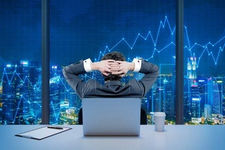 Photo pour Vue arrière d'un commerçant relaxant assis devant une fenêtre, ordinateur portable derrière lui. Nuit vue sur New York. Graphiques en arrière-plan. Un concept de trading forex . - image libre de droit
