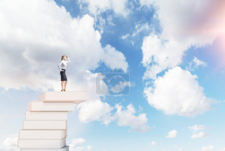 Photo for Young woman with a hand on her head standing on a pile of books, looking in front, blue sky at the background. Concept of dreaming. - Royalty Free Image