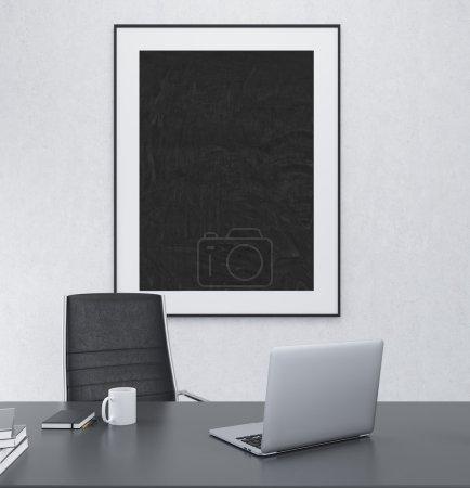 Foto de Un lugar de trabajo con un portátil abierto, taza y datebooks, silla negra en la mesa, un gran rectángulo negro en un marco blanco colgado en la pared detrás. Concepto de decoración de la oficina. Render 3D - Imagen libre de derechos