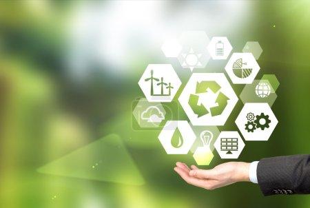 """Foto de Portando signos de diferentes fuentes verdes de energía en forma de hexaedro, un signo de """"reducir, reutilizar, reciclar"""" en el centro. Fondo verde borroso. Concepto de medio ambiente limpio . - Imagen libre de derechos"""