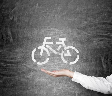Photo for Hand as if holding a bicycle drawn on the blackboard. Concept of eco traveling. - Royalty Free Image