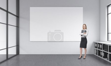 Photo pour Young businesswoman with a folder standing in office space with no furniture except floor shelves for folders and a blank white poster on the white wall, window to the right. Concept of a new office - image libre de droit