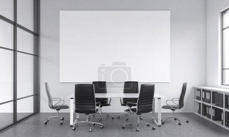 Photo pour Une salle de réunion pour six personnes, des chaises disposées autour de la table, une affiche blanche vierge au-dessus de la table, fenêtre à droite, des étagères sous elle. Concept de négociations. Rendu 3d. - image libre de droit