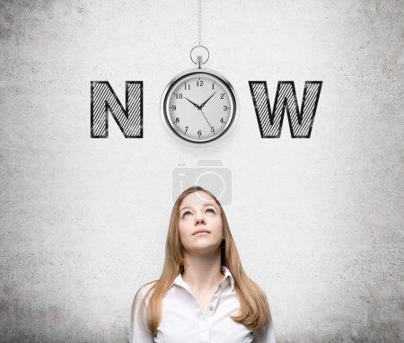 """Photo pour Une jeune femme qui regarde vers le haut en pensant aux opportunités actuelles et au temps. Une montre de poche et le mot """"maintenant"""" sur sa tête. Contexte concret. Vue de face. Concept du moment présent . - image libre de droit"""