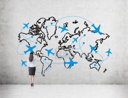 A woman drawing a map demonstaring flight destinations around the globe on a concrete wall in front of her.