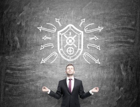 A man in the posture of meditation with eyes closed standing under a shield drawn on the blackboard, arrows around the shield as if rebounding from it.