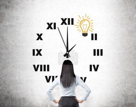 Photo pour Une femme avec les mains sur les hanches debout devant une horloge peinte sur un mur de béton, une ampoule au lieu de 1 sur l'horloge. Vue de derrière. Concept d'avoir et idée à temps . - image libre de droit