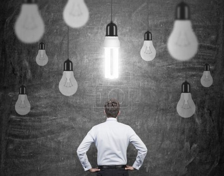 Photo for A man with hands on hips standing in front of a black wall, many different bulbs hovering from above, the energy-saving bulb shining brightly. Back view. Concept of having an idea. - Royalty Free Image