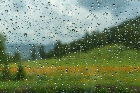 Photo pour Vue du paysage montagneux avec forêt, prairie et fleurs à travers la vitre de la voiture couverte de gouttes de pluie - image libre de droit