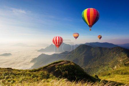 Photo pour Des montgolfières colorées survolant la montagne - image libre de droit