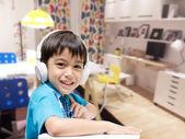 Malý chlapec s headsetem dělat úkoly v místnosti