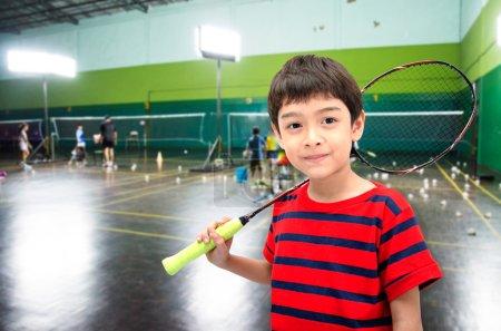 Photo pour Petit garçon prenant raquette de badminton en cours d'entraînement à la salle de gym - image libre de droit