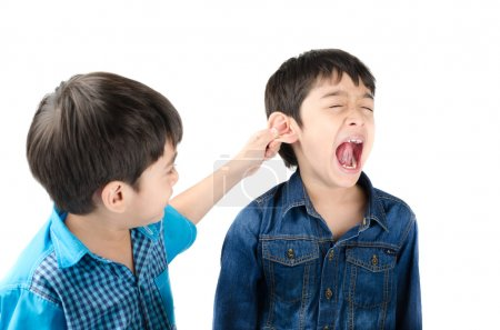 Little sibling boy fighting by pulling ear his brother on white