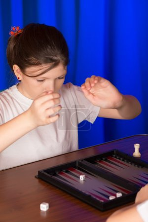 Girl playing a board game called Backgammon