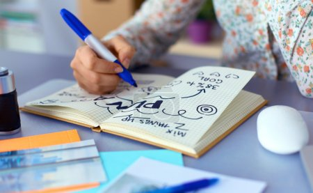Photo pour Jeune femme écrit au journal sur une table blanche  . - image libre de droit