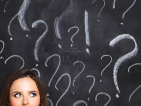 Photo for Young girl with question mark on a gray background . - Royalty Free Image
