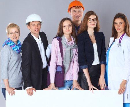Photo pour Heureux groupe de personnes de différentes professions tenant un panneau d'affichage vierge - image libre de droit