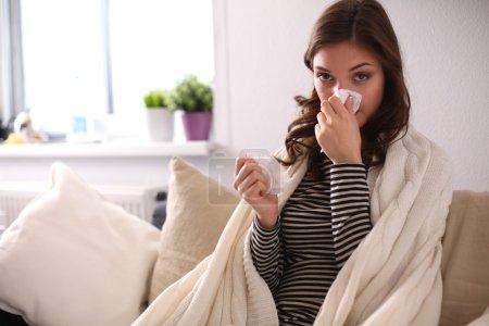 Photo pour Portrait d'une femme malade se mouchant alors qu'elle était assise sur le canapé . - image libre de droit