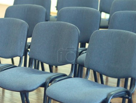 Empty classroom with many armchairs .