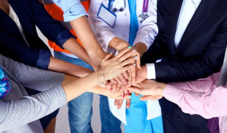 Photo for Portrait of people with various occupations putting their hands on top of each other - Royalty Free Image