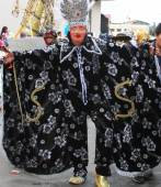 Masked Figure in Black Costume in Carnival Parade