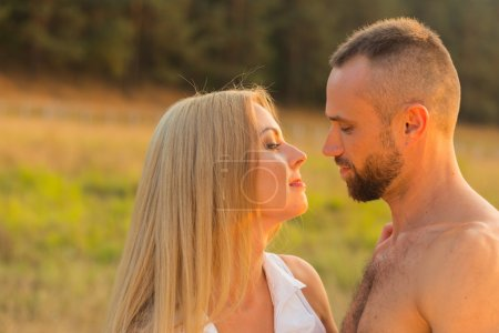 Photo for Man and woman embrace tenderly in the field. Love and sincere feelings. Beautiful young couple. Photo for social magazines, posters and websites. - Royalty Free Image