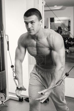 Man makes exercises at  gym