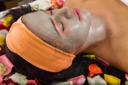 Photo pour Beautiful woman with facial mask at beauty salon.Pretty woman receiving facial massage.Spa therapy for young woman receiving facial mask at beauty salon - indoors - image libre de droit
