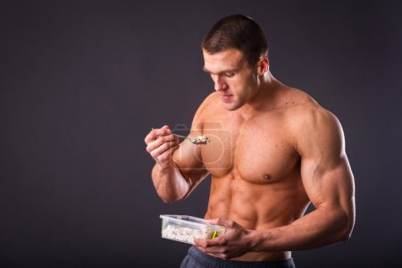 Muscular man eating healthy food - rice on dark ba...