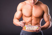 Muscular man eating healthy food